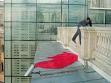 Martin Zet přelézá zábradlí Paláce lidu, aby na fasádu znovu zavěsil rudou vlajku USA, repro: Record