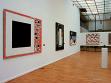 Pohled od instalace polské malby 80. a 90. let 20. století. Zleva obrazy Marka Sobczyka, Jarosława Modzelewského a Włodzimierze Pawlaka